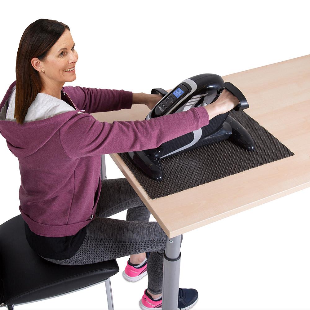 Sie trainieren bequem im Sitzen – die Bodenmatte sorgt für den sicheren Stand des Elektro-Mini-Heimtrainers.